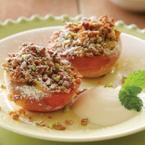 Grilled peaches with berry sauce and pistachio crumble topping