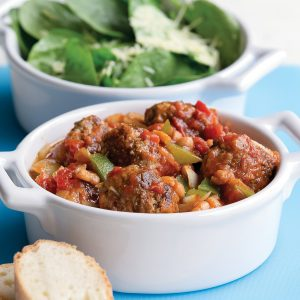 Mini meatballs in a baked bean sauce with leafy green salad and crusty bread