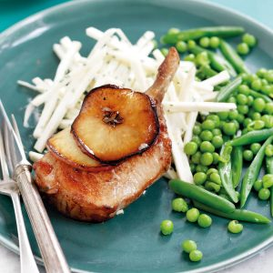 Pork cutlets with sliced red apple and maple syrup
