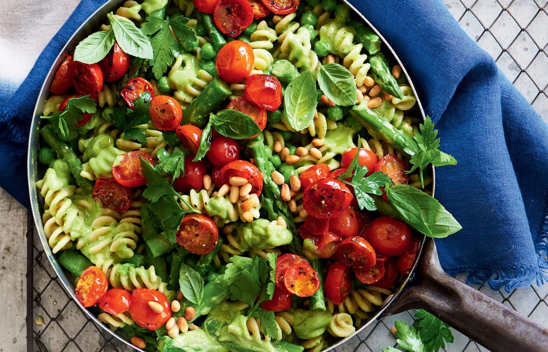 Avocado pesto pasta with peas, asparagus and roasted tomatoes
