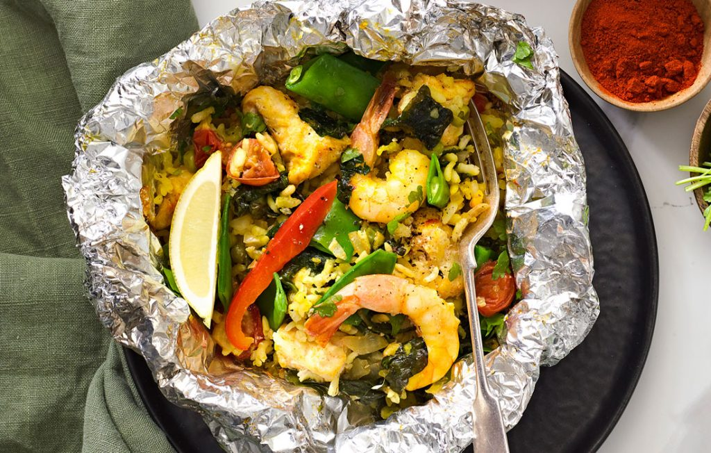 Foil packet with rice, prawns vegetables, lemon and fresh herbs on a marble table top with a dish of paprika and fresh parsley.