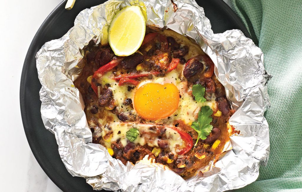 Foil packet with black and kidney beans, vegetables, melted cheese and egg with avocado salsa on the side.