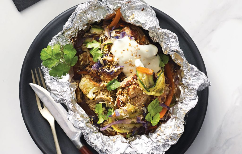 Foil packet with chicken, yohurt, vegetables, seeds, frsh herbs and rice on a black plate.