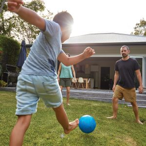 Boy kicking blue ball to father to represent men's health