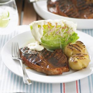 Barbecued lamb chops with potatoes and iceberg lettuce salad