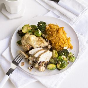 Prune and cream cheese-stuffed chicken breast with roasted greens and toasted almonds