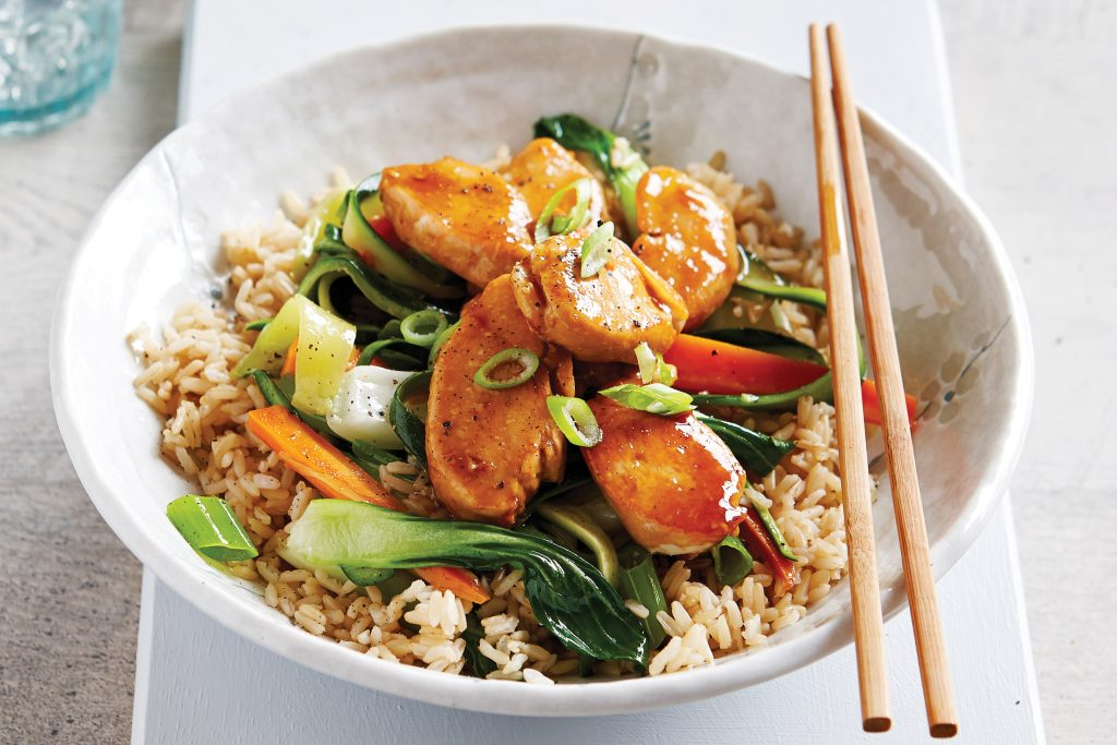 Teriyaki chicken on rice in a bowl with chopsticks
