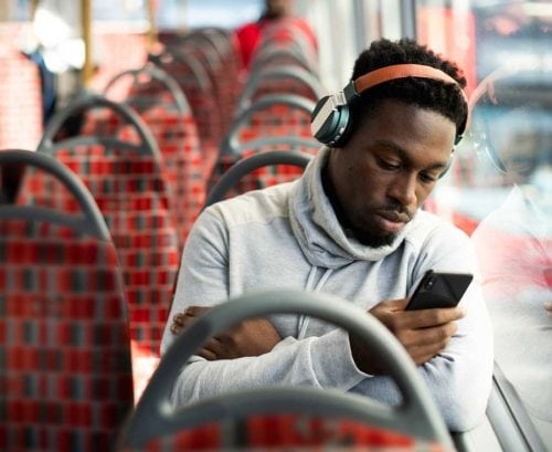 Man on train with headphones and smartphone