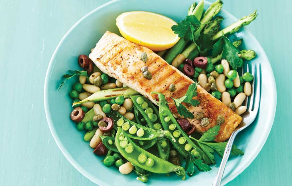 Grilled salmon and peas, beans and asparagus on a light blue plate