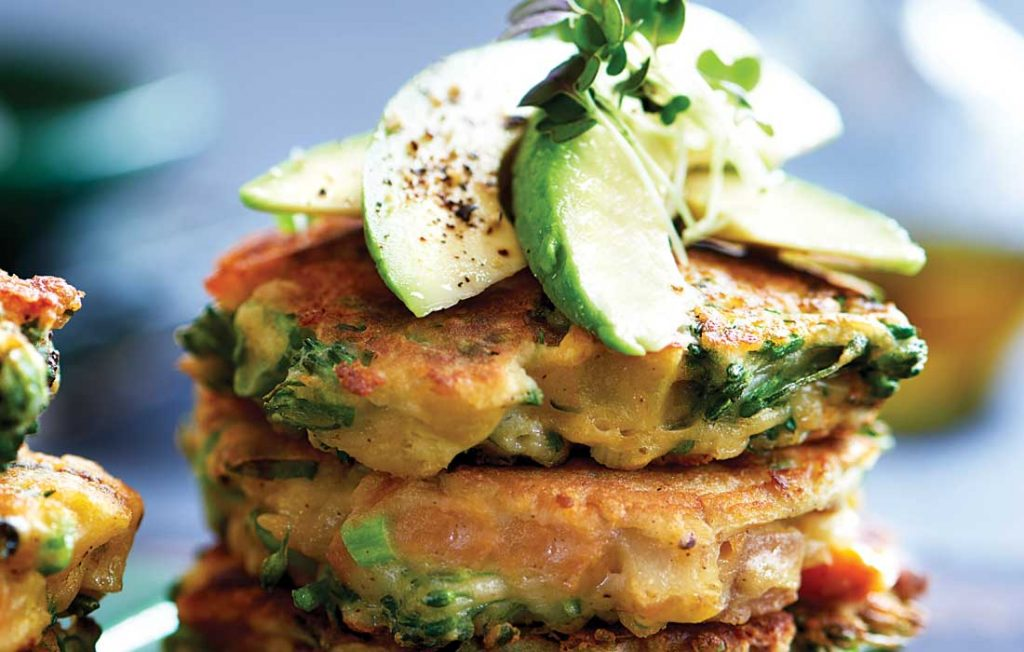 a pile of vegetable fritters topped with avocado