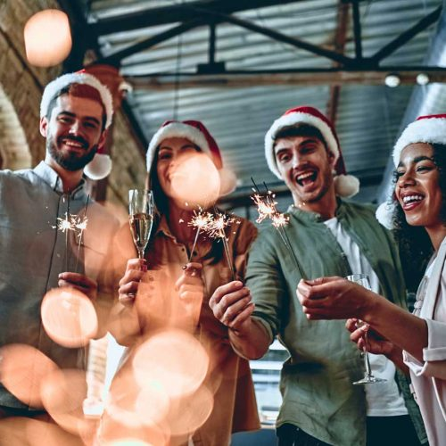 Four people toasting wine with Christmas hats on