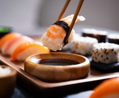 Nigiri on chopsticks with sushi in the background