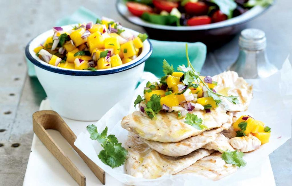 A stack of grilled chicken with a bowl of mango salsa and a bowl of black bean salad