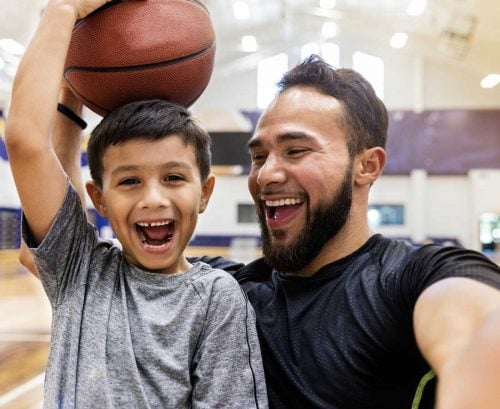 Man and boy laughing with basketball