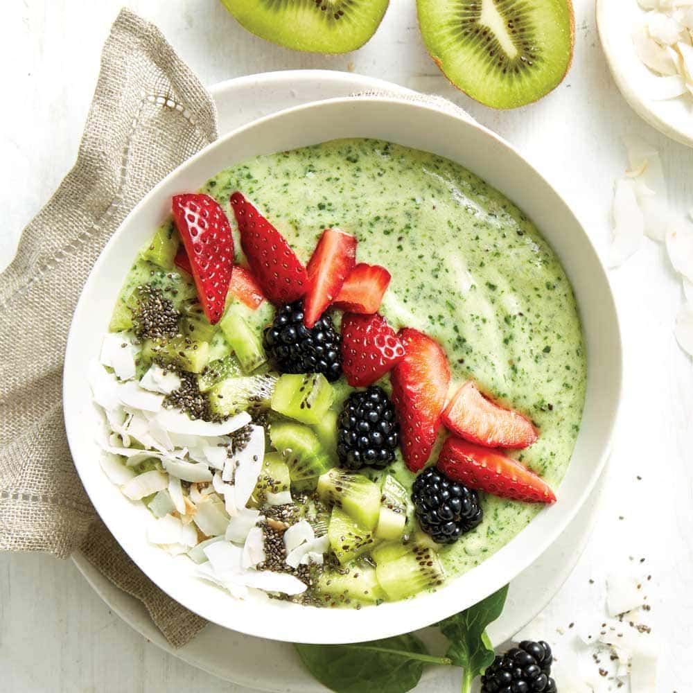 Green smoothie decorated with strawberries,blackberries and kiwifruit