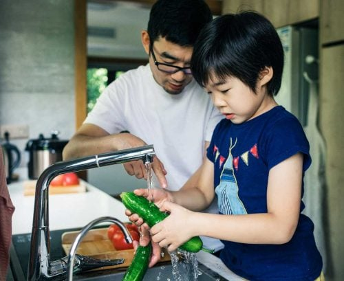 Dad and daighter washing vegetables