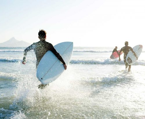 surfers running into the sea