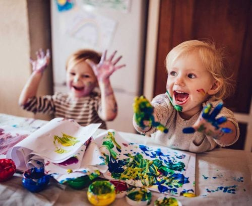 Two small kids finger painting