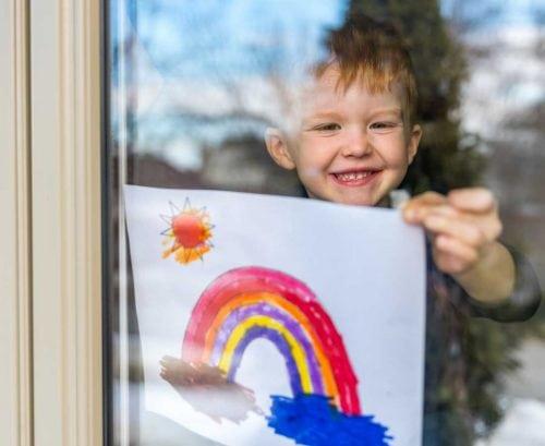 little boy holding a rainbow up in a window