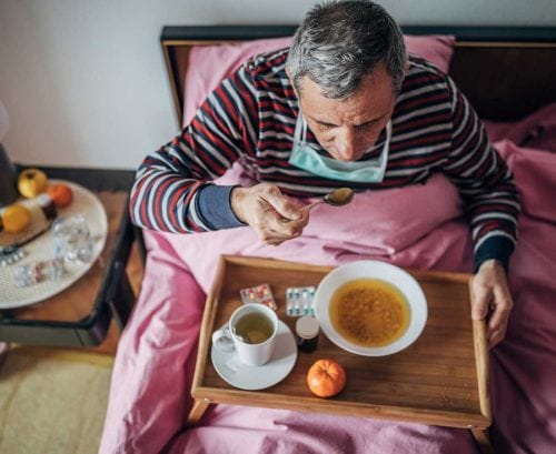 man with coronavirus at home eating soup
