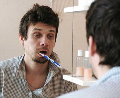 tired man brushing teeth in bathroom mirror