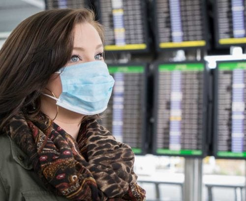 Woman with COVID-19 mask on at airport