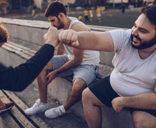 Man with obesity fist bumping friend