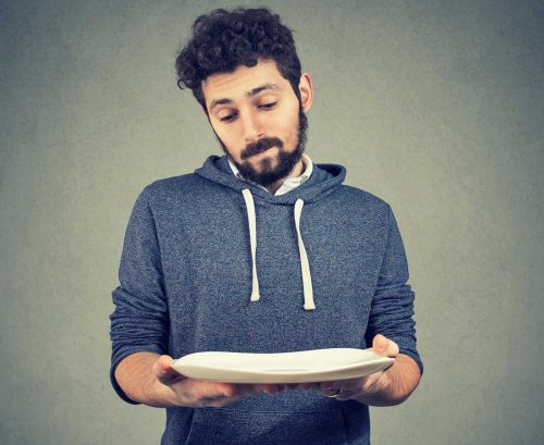 Man holding out an empty plate
