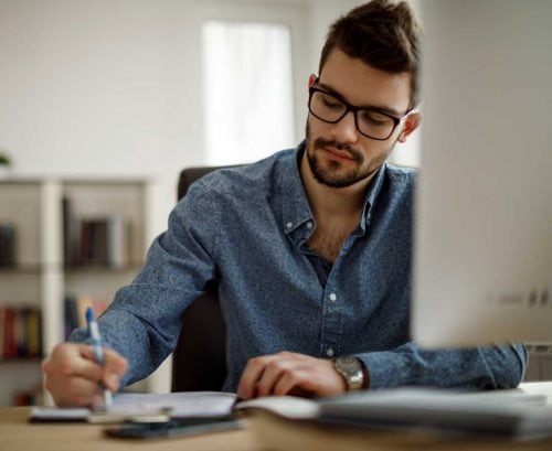 Man in glasses at computer working from home