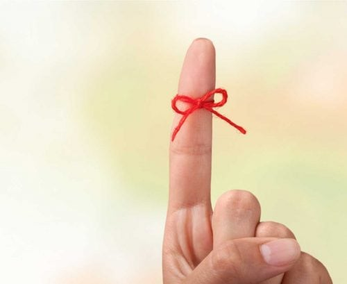 Finger with a red bow tied around it