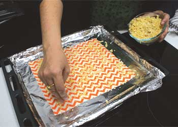 Sprinkiling beeswax on fabric on roasting tray