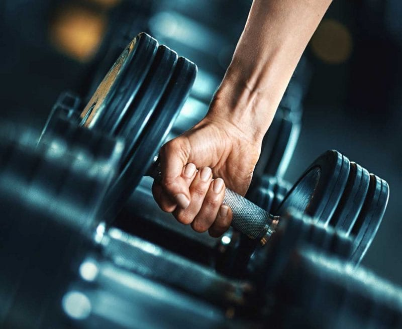Man reaching for dumbell weight