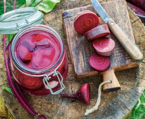 Jar of pickled beetroot and sliced beetroot on a board