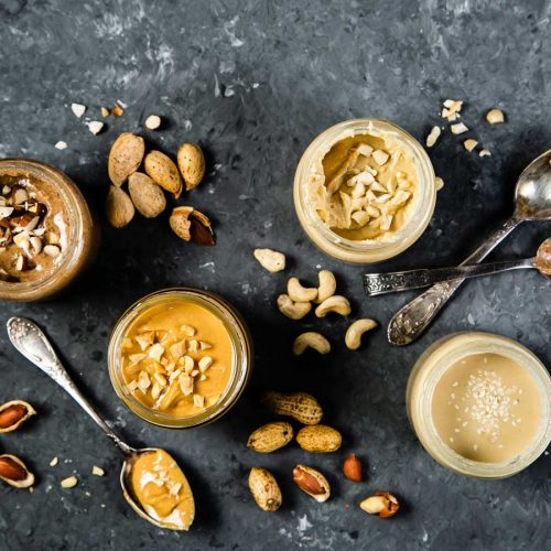 four different types of nut butter in jars