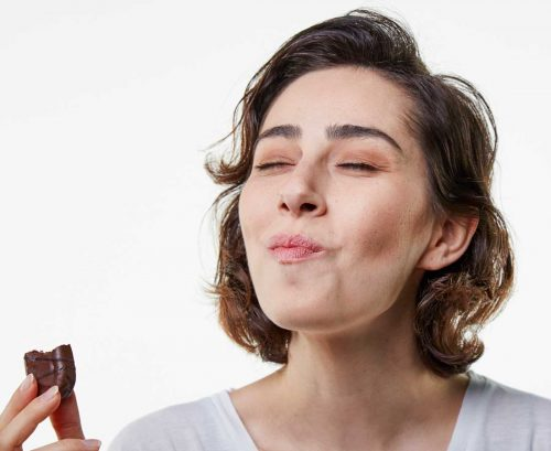Woman eating a chocolate biscuit