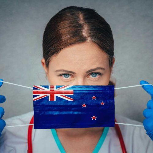 Doctor putting mask on with NZ flag on it