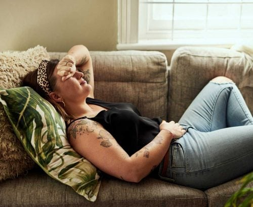 Woman lying on sofa with sore stomach