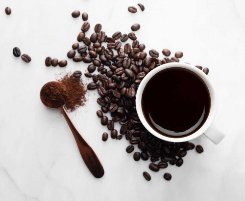 Cup of black coffee with coffee beans and coffee powder