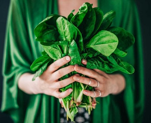 Woman in green holding a bunch of spinach