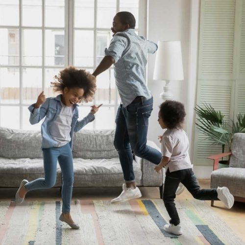 Father and daughters dancing energetically in living room