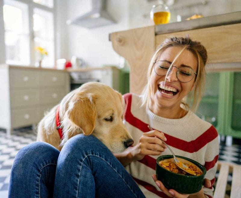 Happy woman eating cereal with dog