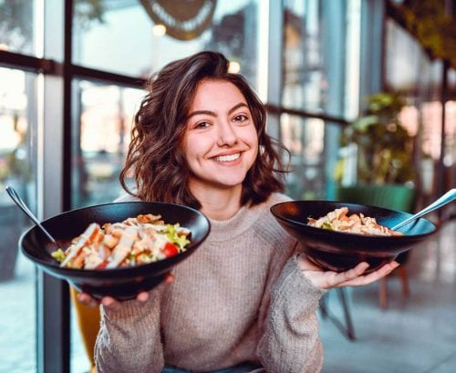 Women holding bowls of food