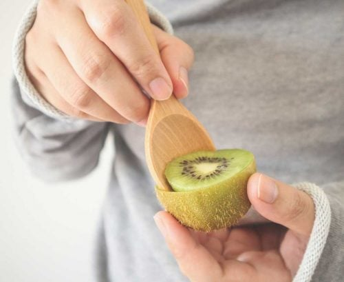 Person scooping out a kiwifruit