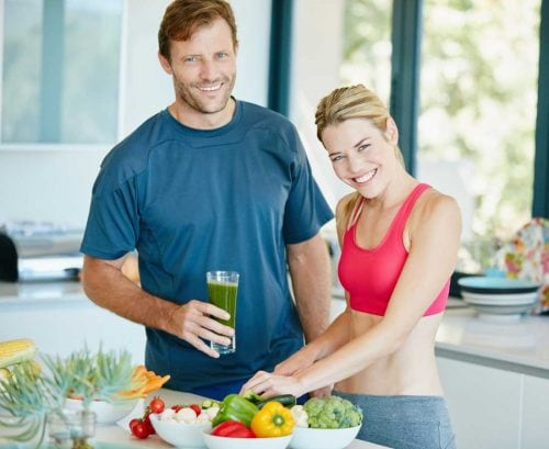 healthy looking couple making green smootihies