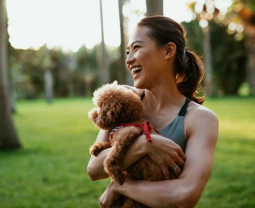 Healthy woman holding dog