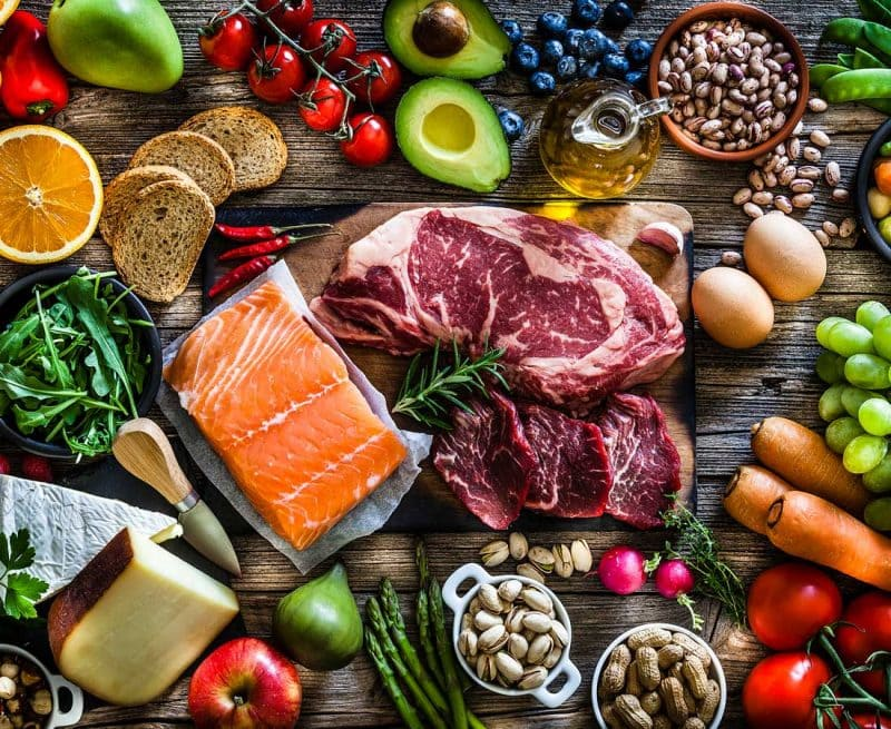 an array of vegetables, fruit, nuts, legumes, fish and meat