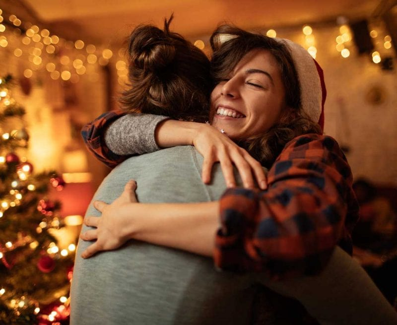 Two women hugging supportively by the Christmas tree