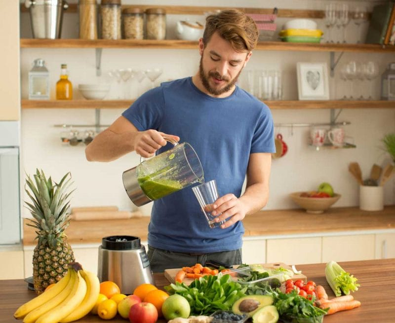 Man making a green smoothie to detox with