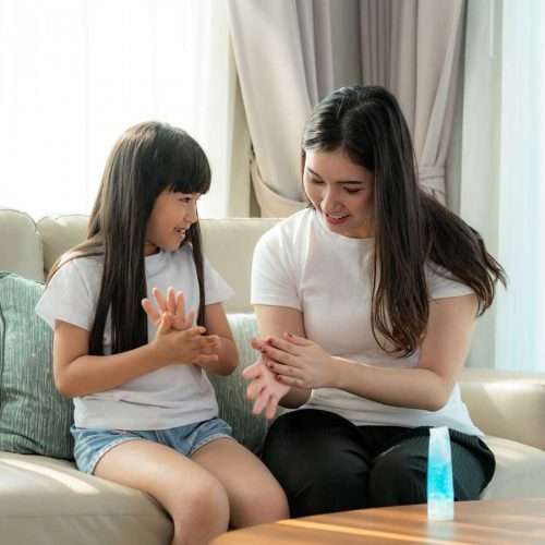 Mother and daughter using hand sanitiser