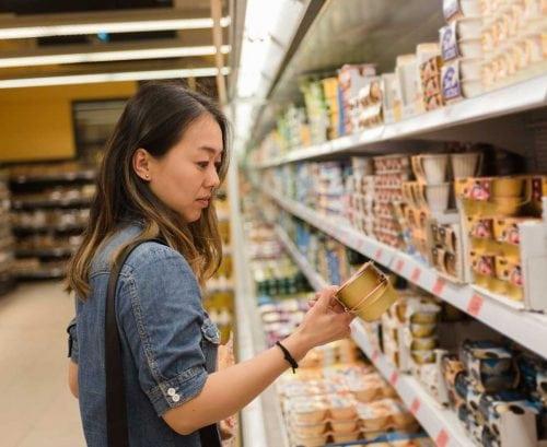 Woman reading yoghurt label in supermarket